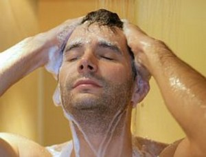 Мужчина моет голову под душем
