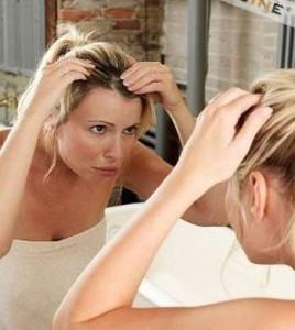 Женщина массирует голову