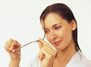 Женщина обрезает кончики волос