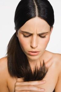 Женщина рассматривает кончики волос