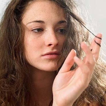 Женщина рассматривает прядь волос