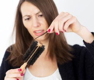 Женщина снимает волосы с расчески