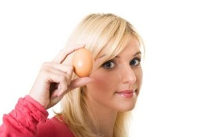 Женщина держит куриное яйцо