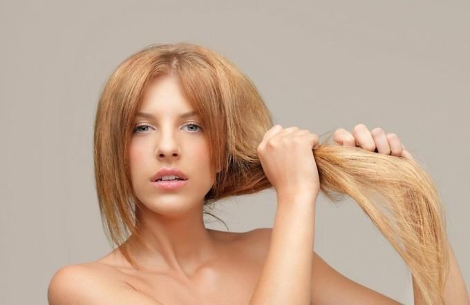 Женщина держит свои волосы