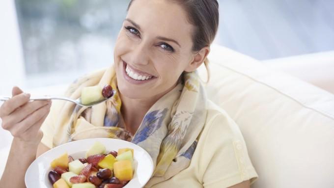 Женщина кушает фрукты и ягоды