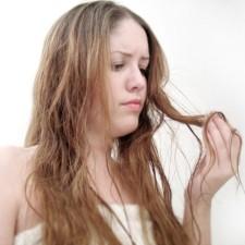 Девушка смотрит на прядь волос
